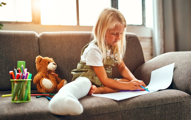 A cute little girl with a broken leg in a cast is sitting on the couch at home and is drawing.