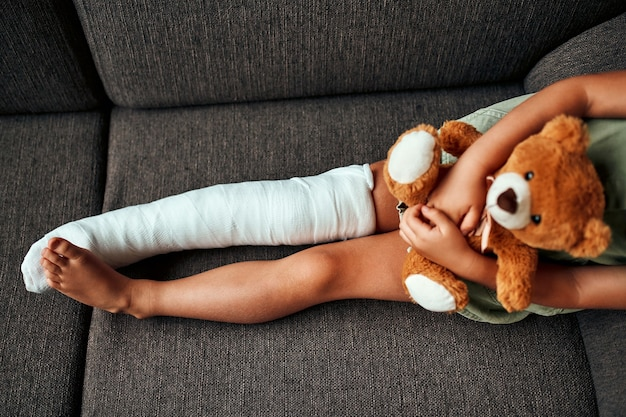 A cute little girl with a broken leg in a cast, sits hugging a teddy bear on the couch at home.