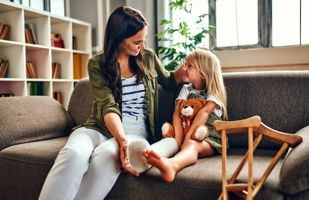 A cute little girl with a broken leg in a cast sits with her mother on the couch hugging a teddy bear at home. there are crutches near the sofa for quick rehabilitation.