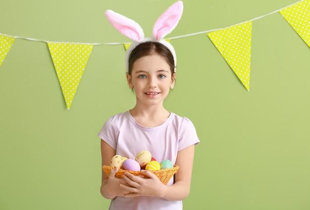 色の表面にウサギの耳とイースターエッグを持つかわいい女の子