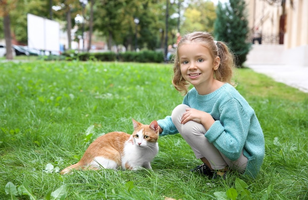 Cute little girl with cat outdoors