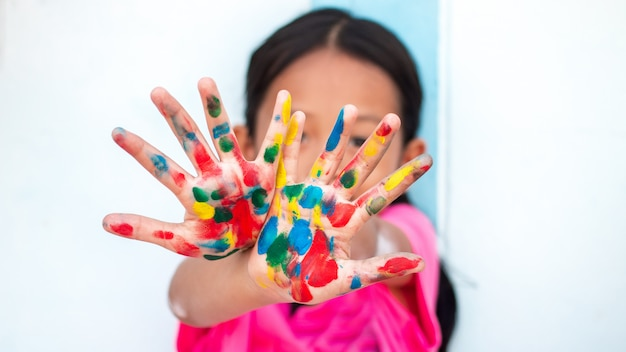 Cute little girl with colorful painted hands on wall background