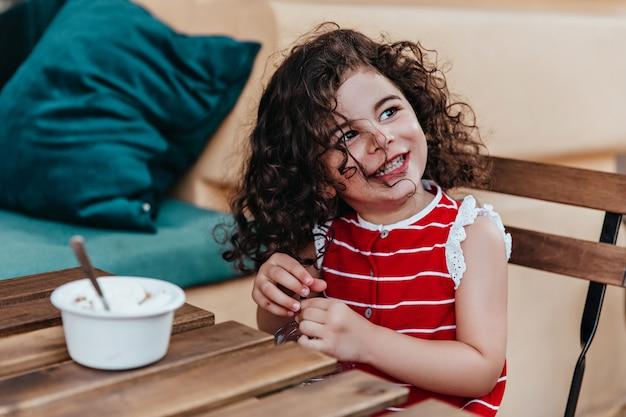 屋外レストランに座っている巻き毛のかわいい女の子。カフェでアイスクリームを食べるかわいい子供の肖像画。
