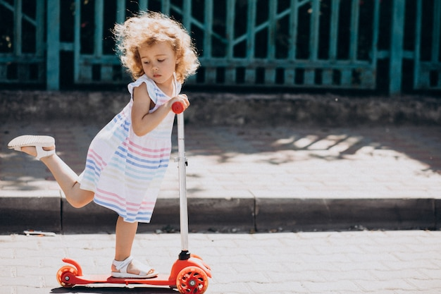 Cute little girl with curly park riding scooter