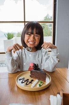 디저트 음식을 먹을 준비가 된 귀여운 소녀 프리미엄 사진