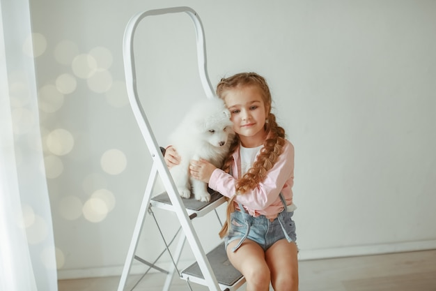 Милая маленькая девочка с собакой дома