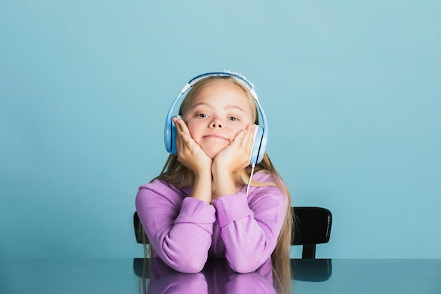 Cute little girl with down syndrome listening to music