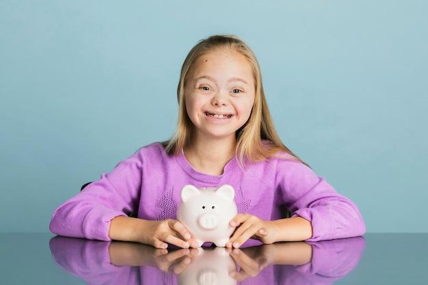 다운 증후군을 앓고 있는 귀여운 소녀가 돼지 저금통에 돈을 저축하고 있습니다.