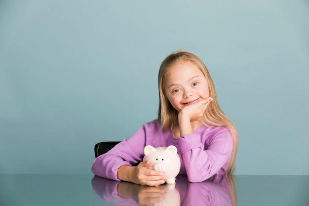 Cute little girl with down syndrome saving money in a piggy bank