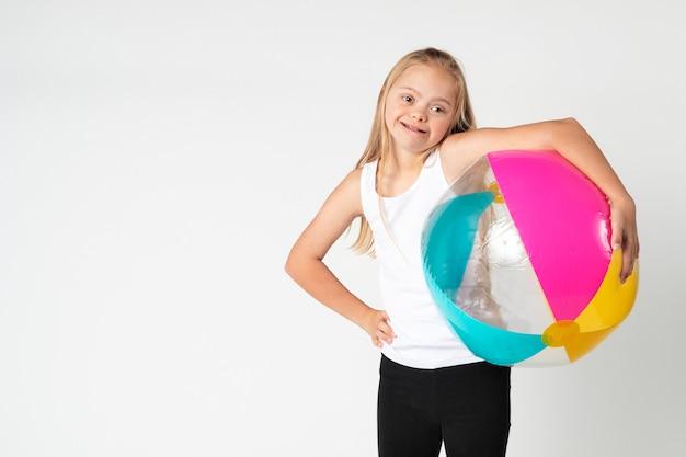 비치볼을 들고 다운증후군을 앓고 있는 귀여운 소녀
