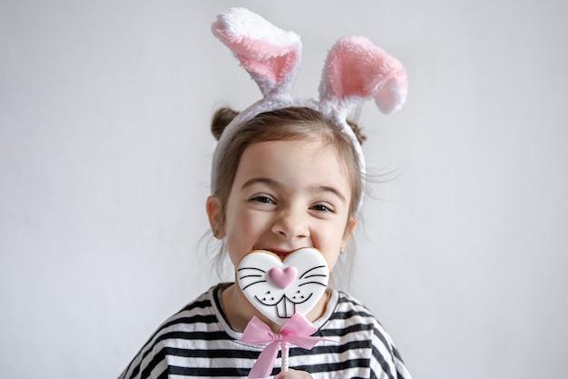 Милая маленькая девочка с пасхальными пряниками на палочке и декоративными кроличьими ушками на голове Premium Фотографии