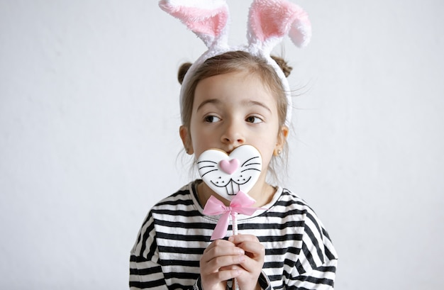 Cute little girl with easter gingerbread on a stick and decorative bunny ears on her head