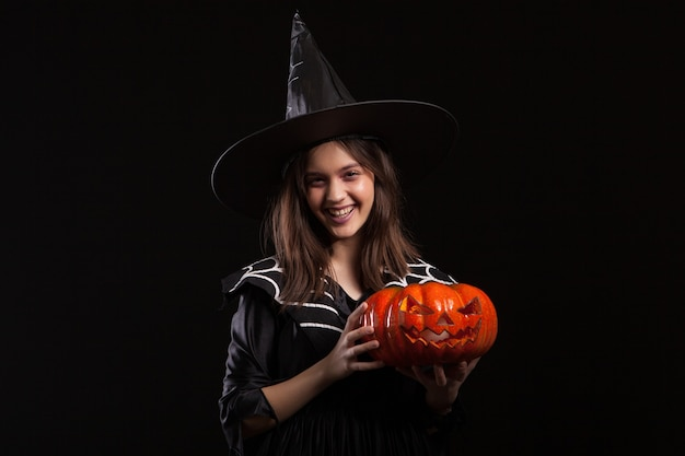 Cute little girl with a evil laugh doing sorcery with a pumpking for halloween. adorable kid in a witch costume for halloween.