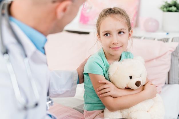 Милая маленькая девочка с пушистой игрушкой смотрит на своего врача с улыбкой, слушая его советы в медицинском кабинете