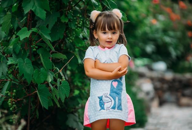 手を組んでかわいい女の子が緑のブドウの近くに立っています。