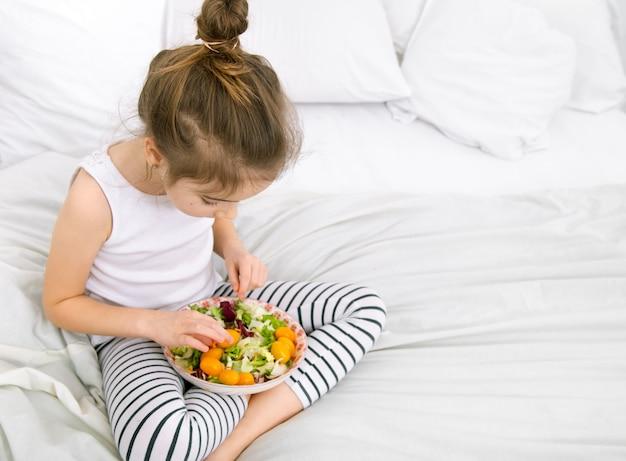 光の果物と野菜でかわいい女の子。