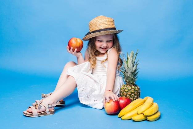 Cute little girl with fruits isolated on a blue wall