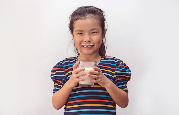 Cute little girl with glass of milk
