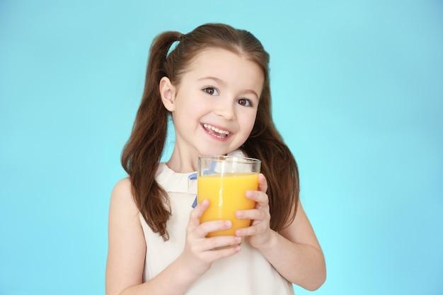 色の表面にジュースのガラスを持つかわいい女の子