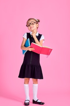 Милая маленькая девочка в очках и книгах на розовом фоне