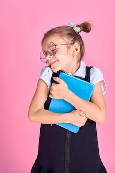 ピンクのスペース、テキストのためのスペースのメガネと本を持つかわいい女の子