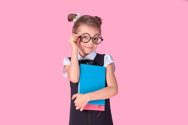 Cute little girl with glasses and books on pink space, space for text. reading concept