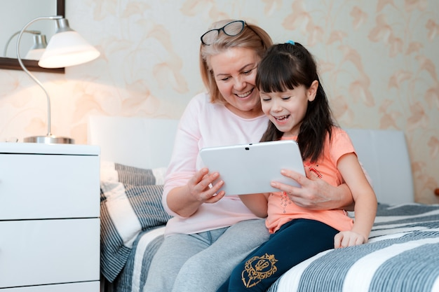 Cute little girl with granny chatting tablet computer in bed at home for online communication