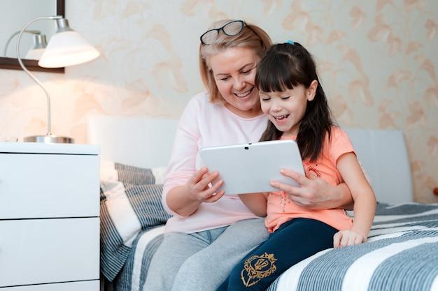 Милая маленькая девочка с бабушкой болтает с планшетным компьютером в постели дома для онлайн-общения