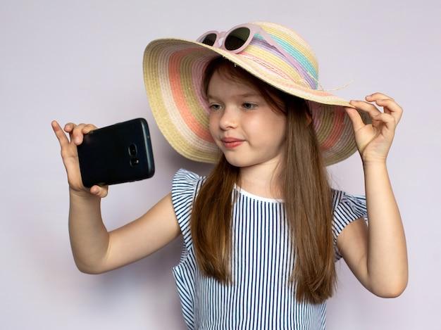 Милая маленькая девочка в шляпе делает селфи со смартфоном