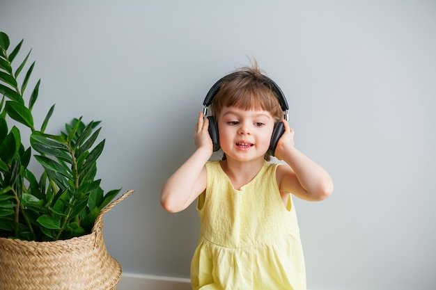 Cute little girl with headphones listening to music and singing at home