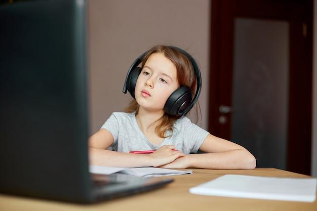 Милая маленькая девочка с наушниками, использующая ноутбук для учебы дома, письма, ответа, онлайн-обучения, образования