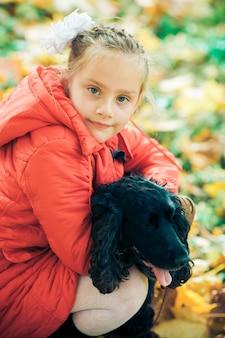 秋の公園で彼女の犬と一緒にかわいい女の子。落ち葉を歩いて犬と一緒に素敵な子。女の子は落ち葉を投げます。幸せな子供時代。秋