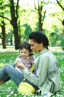 Милая маленькая девочка с матерью, сидя на траве с цветами ромашки в городском парке