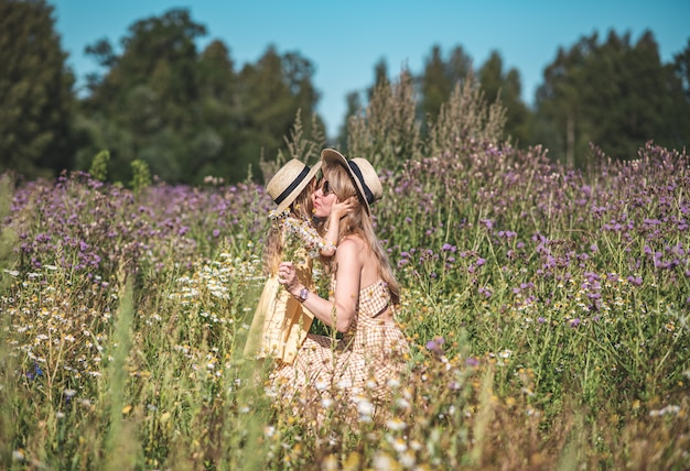 Cute little girl with her mother walking in the flowers field