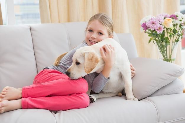 소파에 그녀의 강아지와 함께 귀여운 소녀