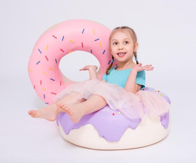 白い背景の上に巨大なドーナツを持つかわいい女の子