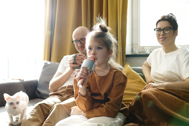 Cute little girl with a karaoke microphone singing for her parents at home