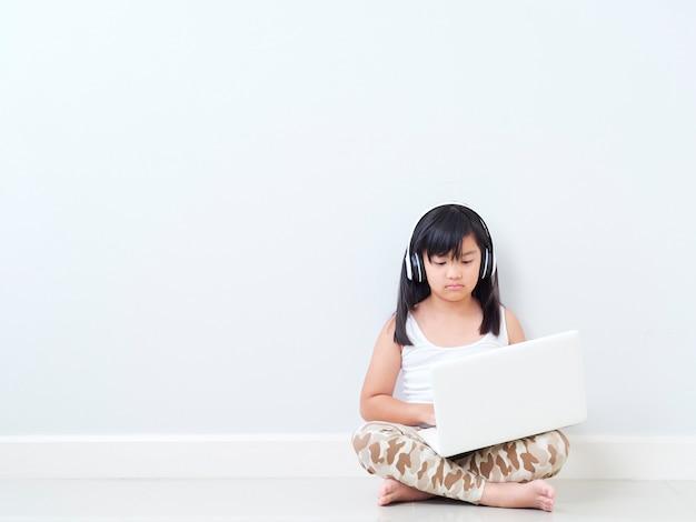 Милая маленькая девочка с ноутбуком дома