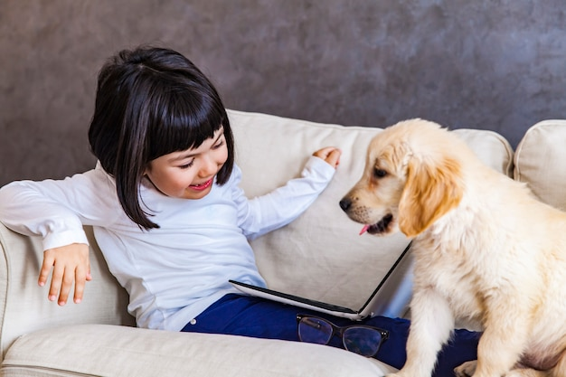 Cute little girl with laptop and gold retriever on sofa