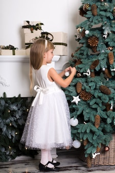Cute little girl with long hair decorating christmas tree. young kid in light bedroom with winter decoration. happy family at home. christmas new year december time for celebration concept