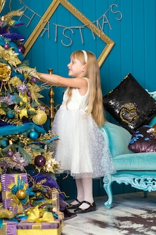Cute little girl with long hair decorating christmas tree