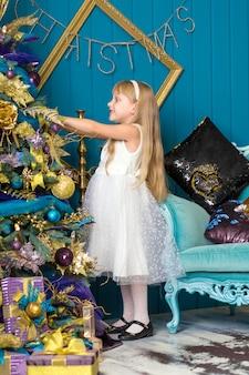 Милая маленькая девочка с длинными волосами, украшать елку