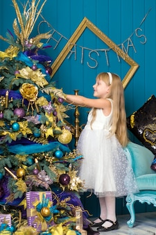 Cute little girl with long hair decorating christmas tree.