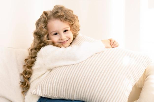 枕を抱き、ベージュのインテリアで笑っている長い髪のかわいい女の子