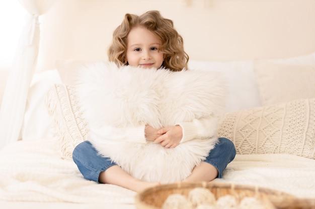 枕を抱いて笑っている長い髪のかわいい女の子