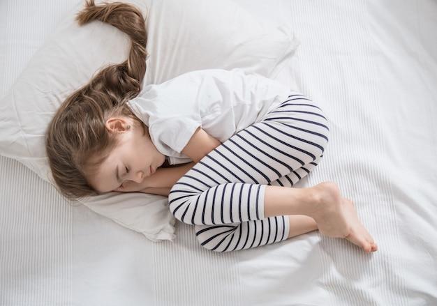 침대에서 자 고 긴 머리를 가진 귀여운 어린 소녀