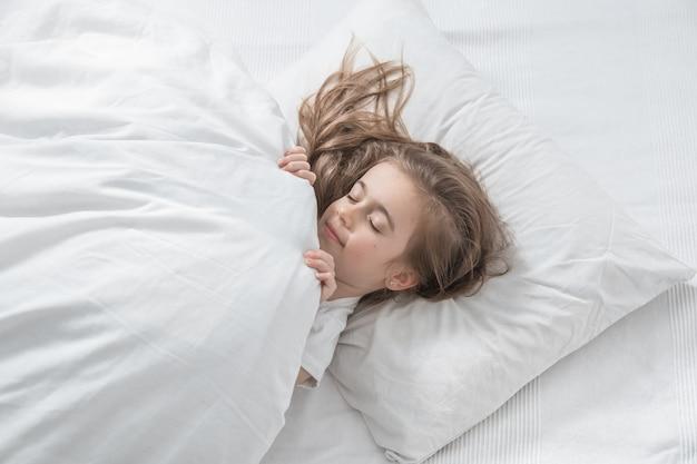 Милая маленькая девочка с длинными волосами, спящими в постели.
