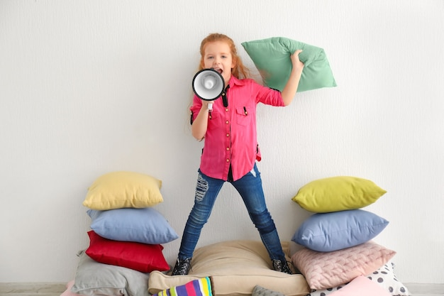 Cute little girl with megaphone standing on pile of pillows indoors