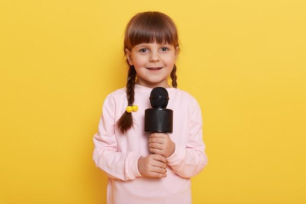 노란색 벽에 고립 된 마이크 포즈, 노래 또는 매력적인 미소로시를 말하는 귀여운 소녀, 땋은 머리와 아이 드레스 캐주얼 옷 콘서트를 준비합니다.