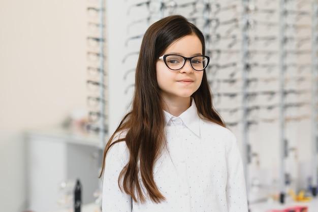 Милая маленькая девочка в новых очках в магазине